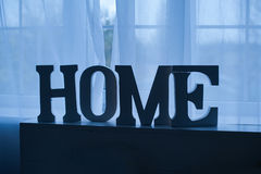 Wooden word home on a table in front of the window Royalty Free Stock Images