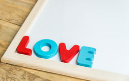 Wooden word LOVE on the corner of White board Stock Photo