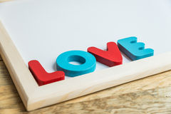 Wooden word LOVE on the corner of White board Royalty Free Stock Images
