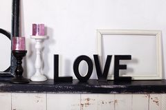 The wooden word is love. On the fireplace are two candlesticks with candles and the wooden word love. Love inscription in wooden l. Etters. Elements of the decor stock images