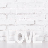 Wooden word love over white brick wall Stock Image