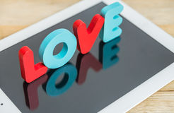 Wooden word LOVE stand on tablet Stock Image