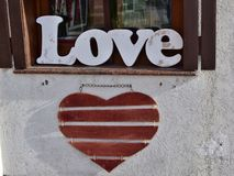 Wooden word `Love` standing on the windowsill and red wooden heart hanging on the wall in the city street stock photography