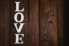 Wooden word love. White wooden word love on brown background Royalty Free Stock Images