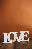 Wooden word love. White wooden word love on brown background Royalty Free Stock Photography