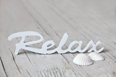 Wooden word relax. Word relax made of wood and shells on wooden background stock photo
