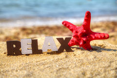 Wooden word 'Relax' with red starfish. At a beach stock photography