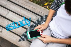 Wooden word study close to woman with smartphone. Letters study, blue letters. Wooden word study close to woman with smartphone. Student stock photography