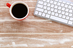Wooden work desk with keyboard. Wooden work desk with computer keyboard and coffee cup stock images