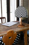 Wooden working table with a polka dot vintage lamp and pillow Royalty Free Stock Photos