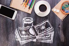 Wooden workplace with money sketch. Wooden desktop with creative money sketch, coffee cup, blank smartphone, supplies and other items Stock Photos