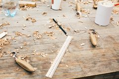 Wooden workshop. Carving spoon from wood, working with chisel. Process of making wooden spoon, chisel, pencil, compass, ruler on. Dirty table with shavings stock photos