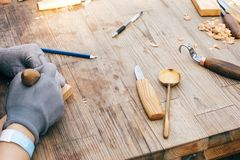 Wooden workshop. Hands carving spoon from wood, working with chisel close up. Process of making wooden spoon, chisel, pencil,. Compass, ruler on dirty table royalty free stock photo