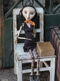Wooden Worn-out Woman Marionette on White Chair.  Stock Images
