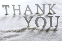 Wooden wthite letter Thank you on the crumpled carpet Stock Photo