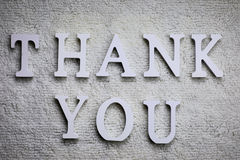 Wooden wthite letter Thank you on the crumpled carpet Royalty Free Stock Photos