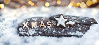 Wooden XMAS letters in a snow scene with blurred lights. Christmas decoration with gingerbread stars and wooden XMAS letters in the snow. Blurred bokeh stock image