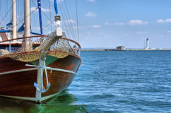Wooden yacht enters sea port Stock Images