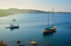 Wooden yacht and some boats are anchored in a beautiful sea bay on a sunset. Konnos bay, Cyprus.  Royalty Free Stock Photography