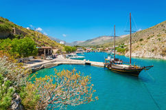 Wooden yacht standing in cosy port on Greek island. With clear blue water, Greece Stock Photography