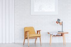 Wooden armchair in dining room. Wooden, yellow armchair next to a table with lamp against white brick wall with silver painting in dining room interior Royalty Free Stock Images