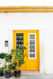 Wooden yellow door. The classical architecture of the Mediterranean (Greece, Italy, Spain, Cyprus, Portugal). Wooden yellow door on the white buildings and stock photos