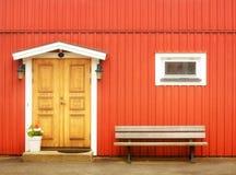 Wooden yellow door in orange colored building Royalty Free Stock Image