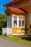 Wooden yellow house with red roof in Scandinavian style Stock Photo