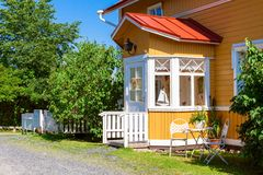 Wooden yellow house with red roof in Scandinavian style. Wooden row yellow house with red roof and white windows in Scandinavian style stock photos