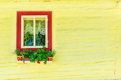 Wooden yellow hut and window with flowers Stock Photo