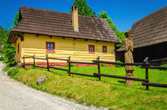 Wooden yelow hut with wood sculpture Royalty Free Stock Images