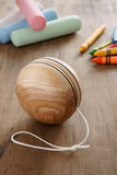 Wooden Yoyo. An old fashioned style wooden yoyo with chalks and wax crayons a retro childhood concept Stock Images