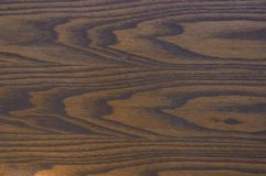 Woodgrain background. An abstract background of stained wood highlighting the beautiful grain in the wood Stock Images