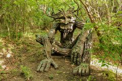 Woodland greenman sculpture setting in forest dappled with sun and shade at Renassiance Festival Muskogee Oklahoma USA 5 21 2016. A Woodland greenman sculpture royalty free stock photos