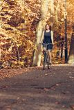 Red haired girl riding on bike in autumnal park royalty free stock images