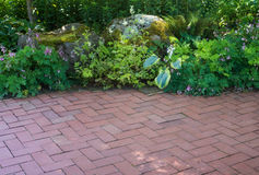 Woodland Patio. A natural shade perennial garden borders a brick patio royalty free stock image