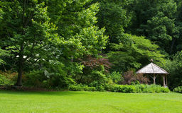 Woodland Rustic Gazebo. Naturalistic garden setting with rustic gazebo and lawn Stock Image