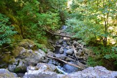 WOODEN BRIDGE OVER CREEK. Woodland setting looking down on a bridge crossing a small creek Stock Photo