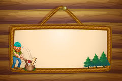 A woodman chopping the woods in front of the hanging frame templ Royalty Free Stock Images