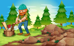 A woodman chopping the woods near the rocks Royalty Free Stock Photography