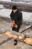 Woodman peels bark from logs, using a chainsaw. Stock Photos