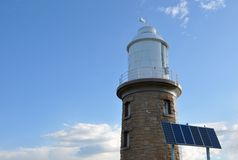 Woodman Point Lighthouse: Old Meets New. Woodman Point Lighthouse with limestone bricks and a white lantern room with wind vane on top towers in the blue sky Stock Photography