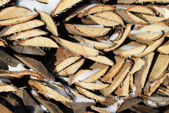 Woodpile. Background of stacked firewood in woodpile powdered white snow Stock Photography