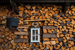 Woodpile decorated with old lantern, cauldron  and wooden heart. In a chalet Royalty Free Stock Photography