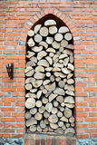 The woodpile of firewood is put in an arch aperture of a brick w Royalty Free Stock Image