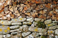 Woodpile on stone wall Stock Photography
