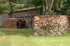 Woodpile on stone wall Royalty Free Stock Photos