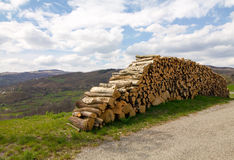 Woodpile w słonecznym dniu blisko drogi na wzgórzach obraz stock