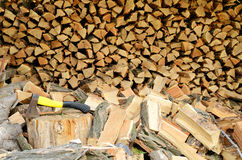 Firewood and ax. Full picture of firewood close-up. The ax in the stump Stock Photos