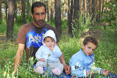 In the woods on a flower meadow sits father with young sons Stock Photography